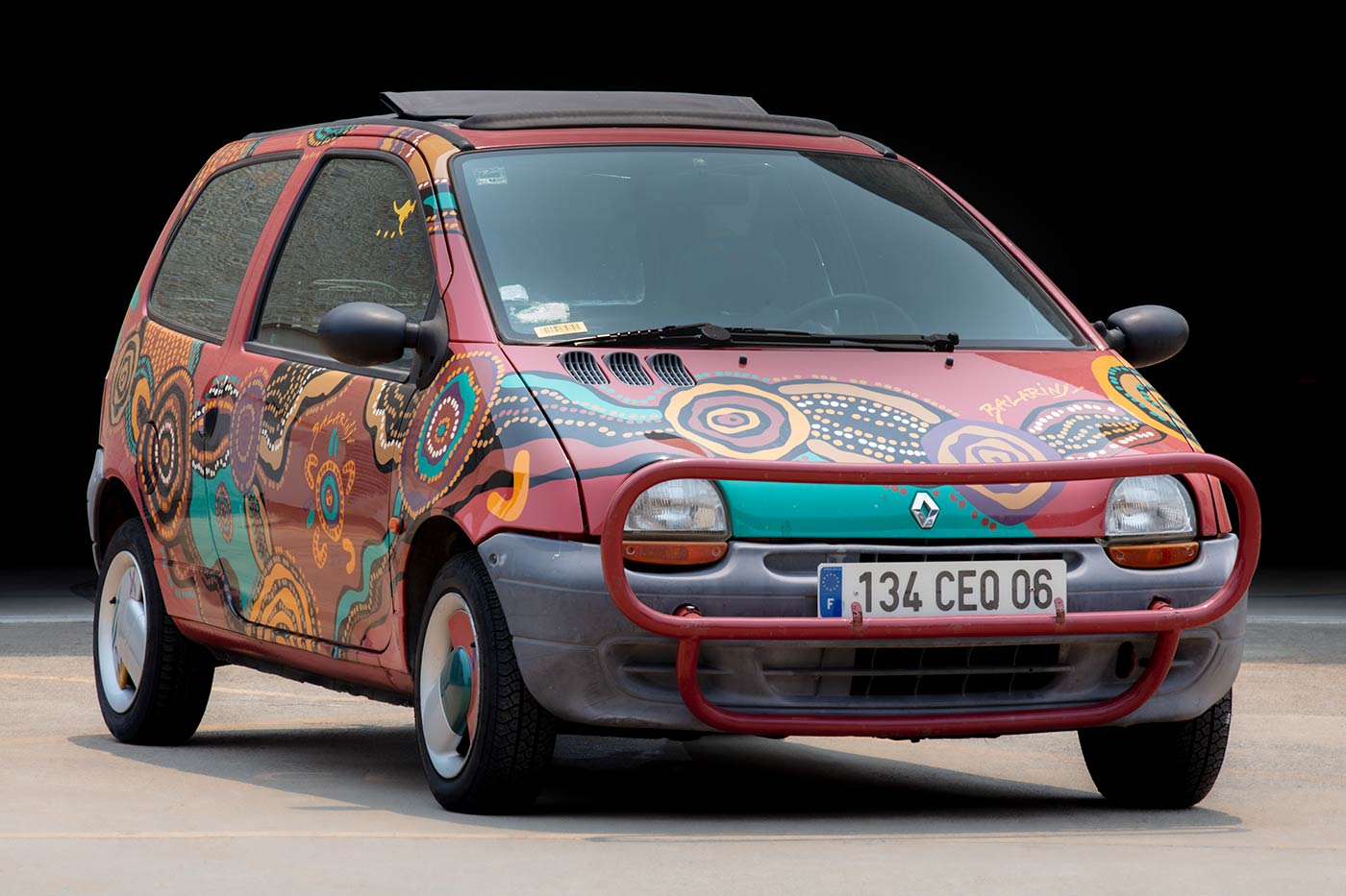 A 1993 Renault Twingo car painted with a Balarinji 'Wunala Dreaming' design. The small car has two doors and a hatch-back, is petrol-driven and left hand drive, and has a bull-bar at the front. The painted design features dotted, circular and line motifs against a red background, and the 'BALARiNji' logo on the front passenger door. - click to view larger image