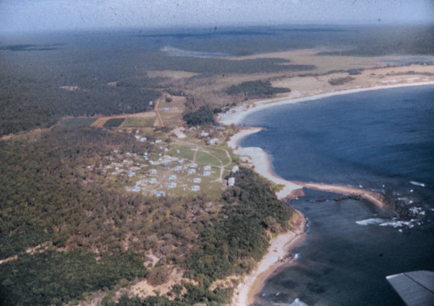 Aerial view of coastal area and bushland with some buildings scattered about.