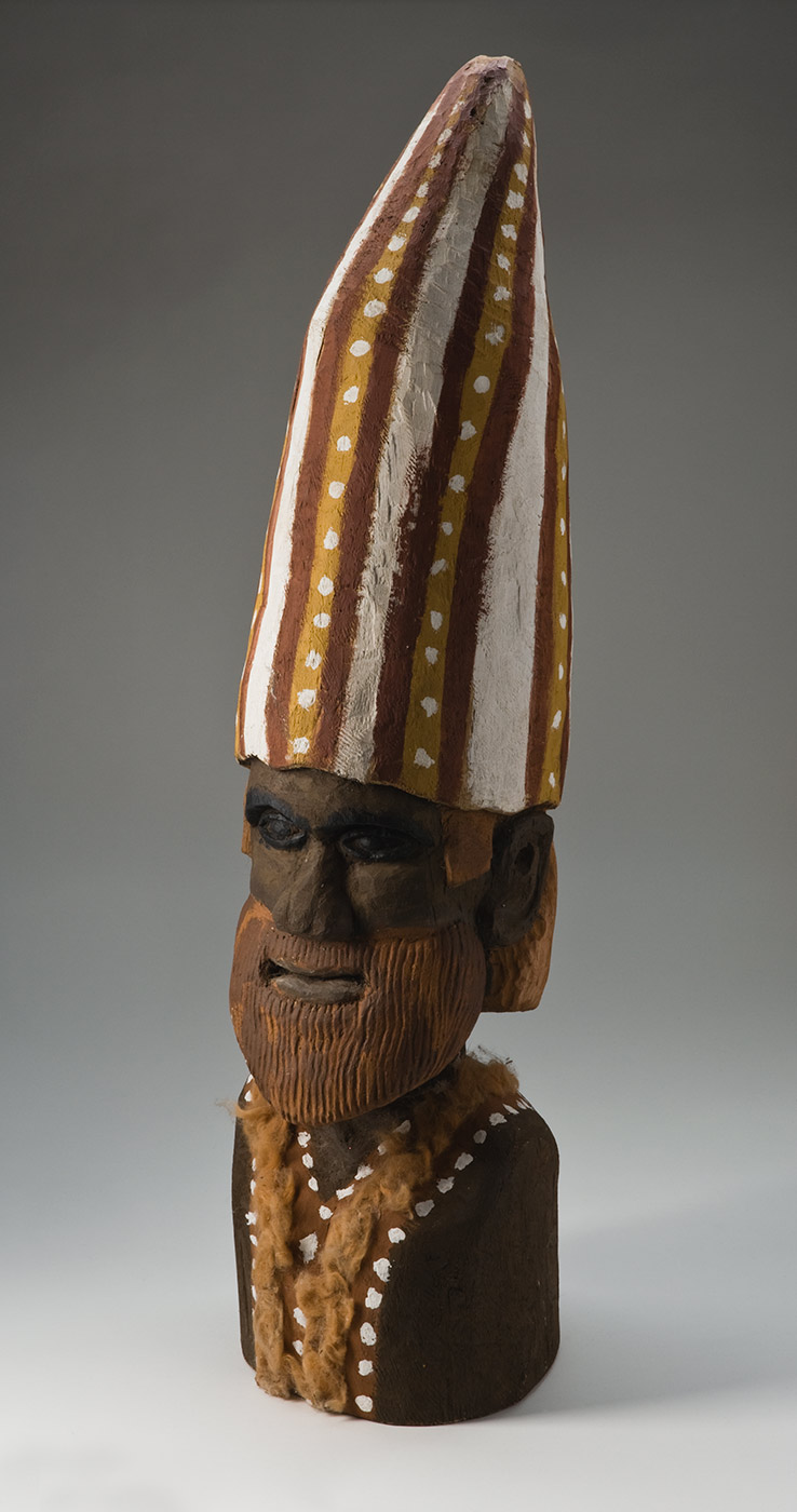 A carved and pigmented wooden bust of a human figure with a pointed hat and body decoration. The face and body of the figure are black-brown with the facial features deeply carved out of the wood, including an
