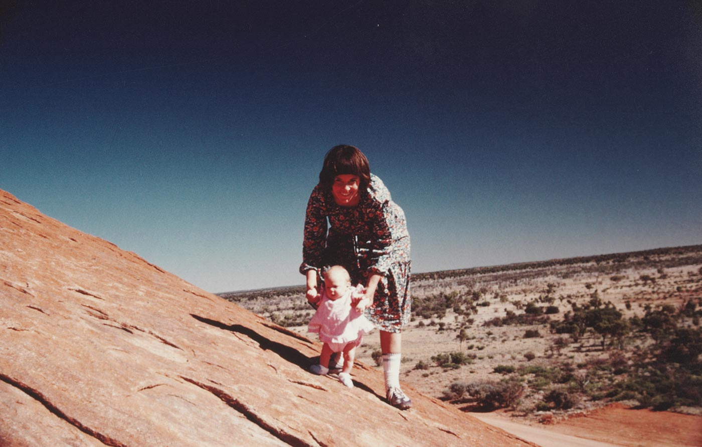 A mother with her daughter poses for the camera while standing on a rock slope in a vast rugged terrain.