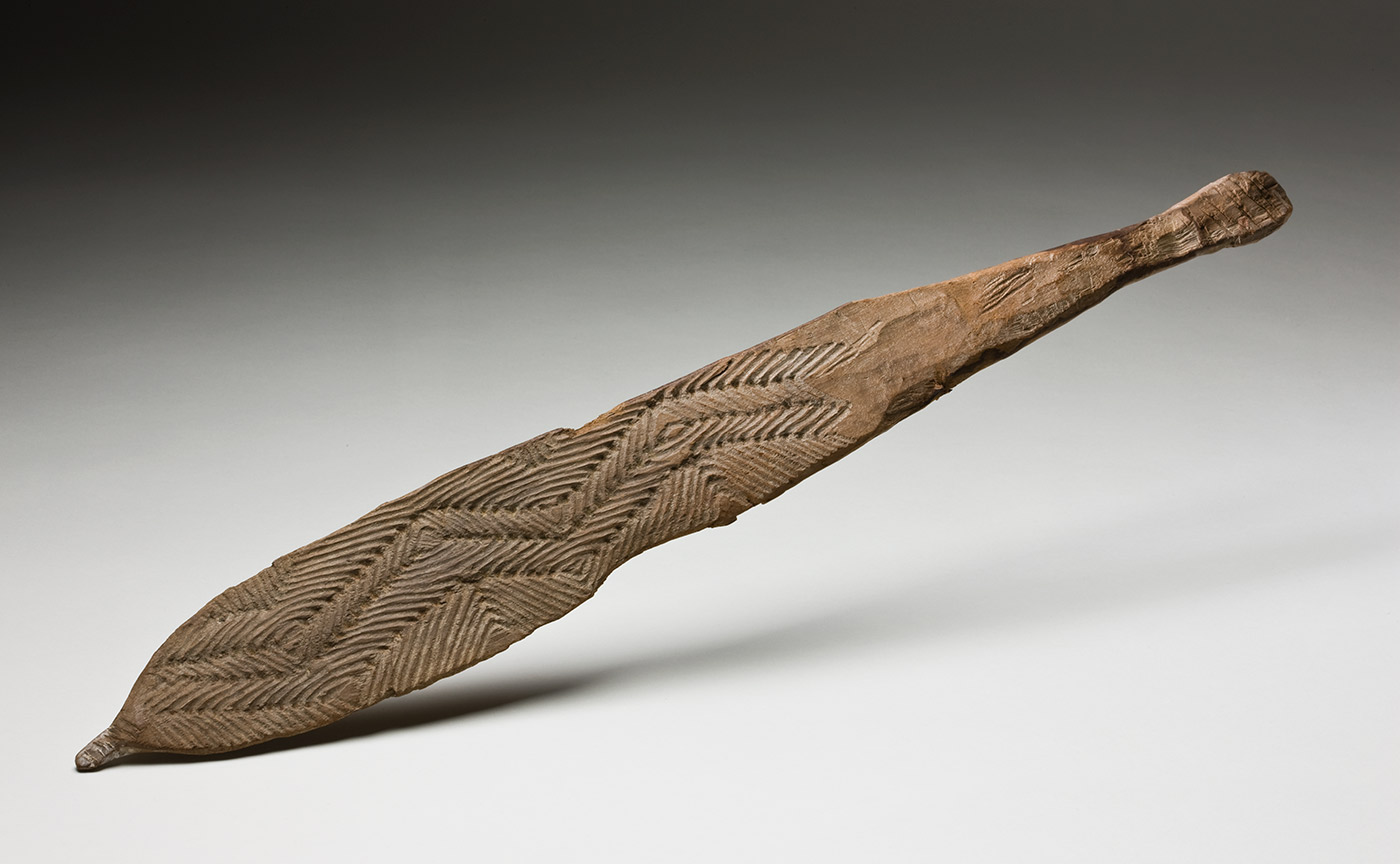 A flat carved wooden spear thrower. One side has a ornate triangular carving toward the proximal end. Remnants of white ochre are present across the wood, particularly at the proximal end where the peg is also missing. The sprear thrower shows signs of water damage and the curved sides have been broken in the centre. - click to view larger image