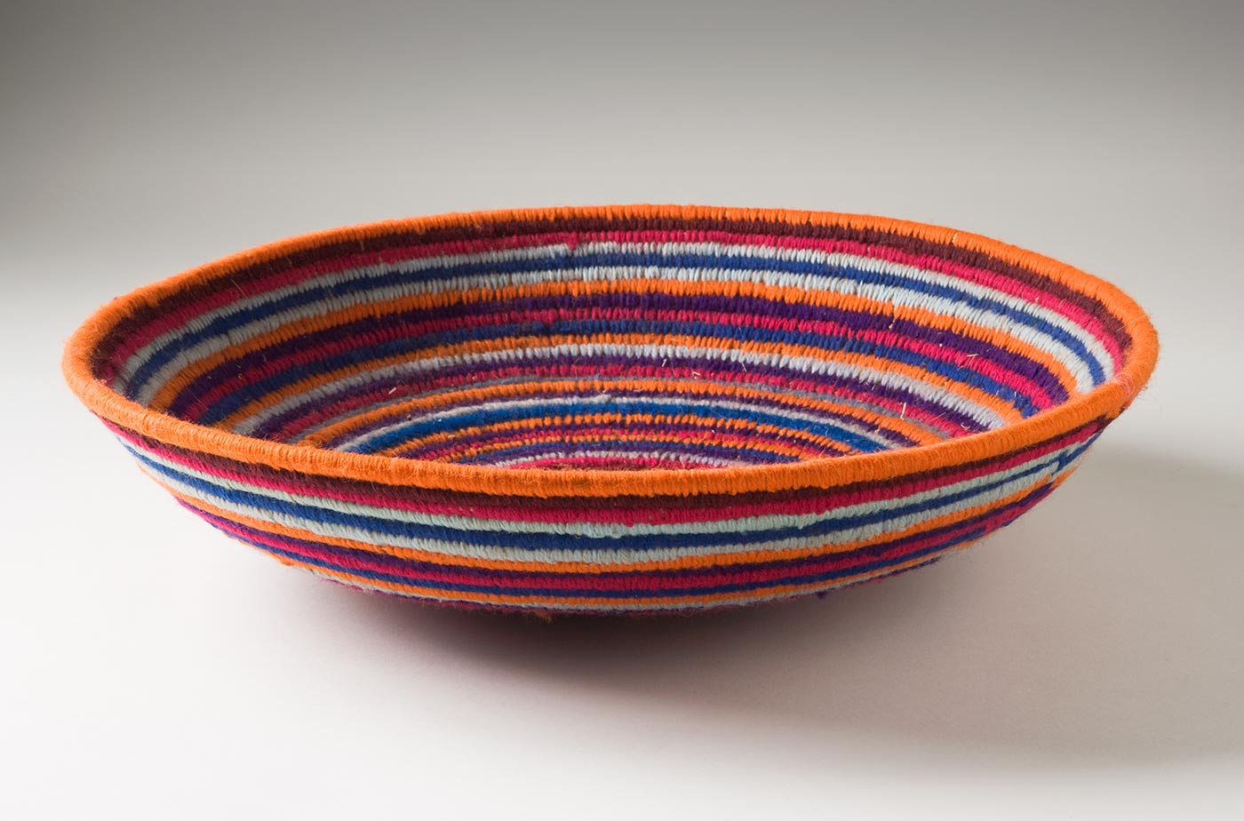 A multi-coloured circular coiled bowl-shaped basket made of yarn and plant fibre. The centre of the basket is in orange yarn followed by horizontal stripes of yarn in dark pink, purple, grey, blue, brown and orange. - click to view larger image