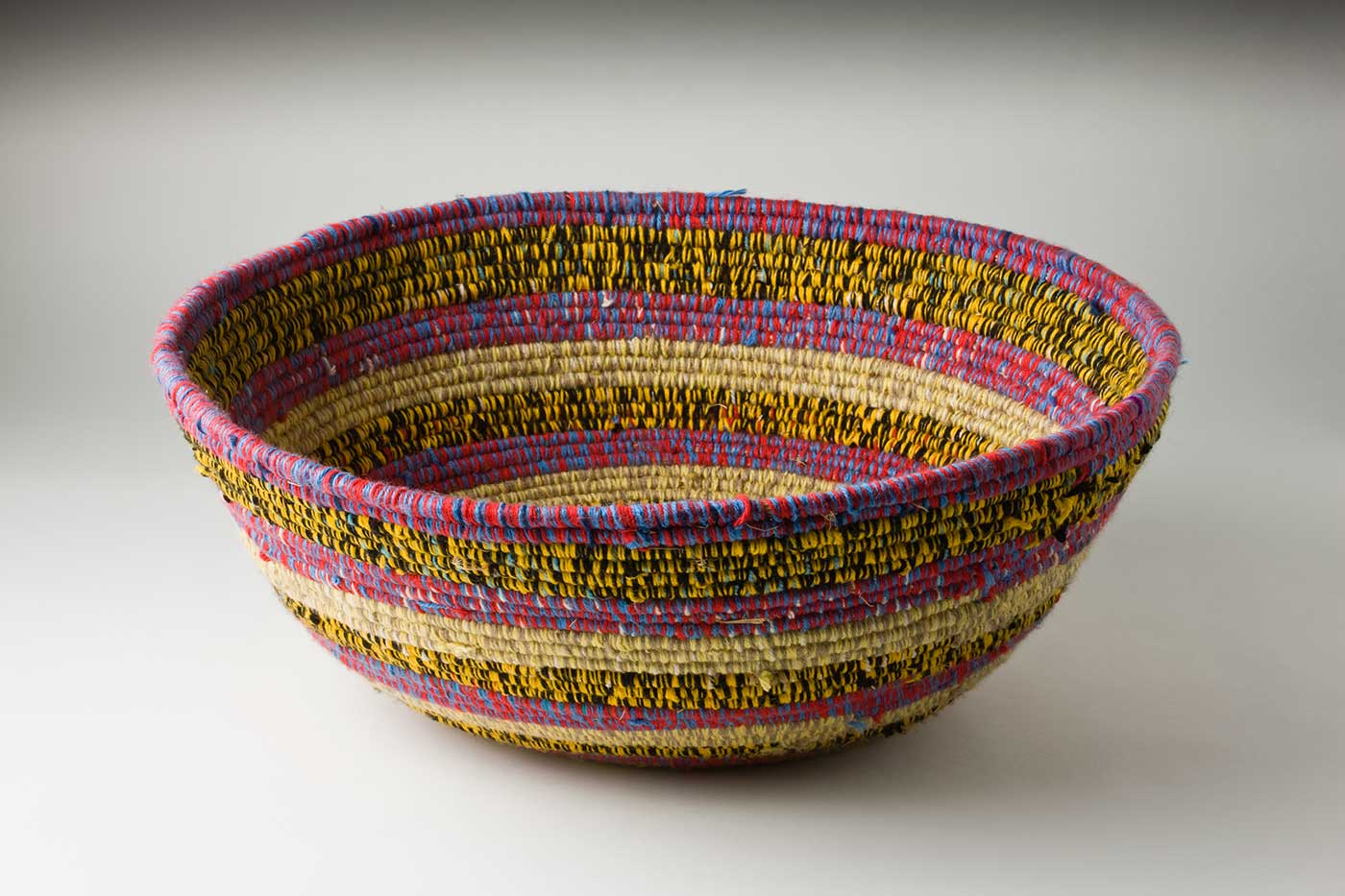 An oval coiled multicoloured yarn and plant fibre basket. The plant fibre in the centre of the basket is covered by purple-yellow yarn, followed by horizontal alternate yarn coverings over the fibre. The yarn colours are green-yellow, tan-yellow, purple-red, yellow-black, green-silver-brown and red-white-brown. The top plant fibre is covered by yellow-black yarn. - click to view larger image