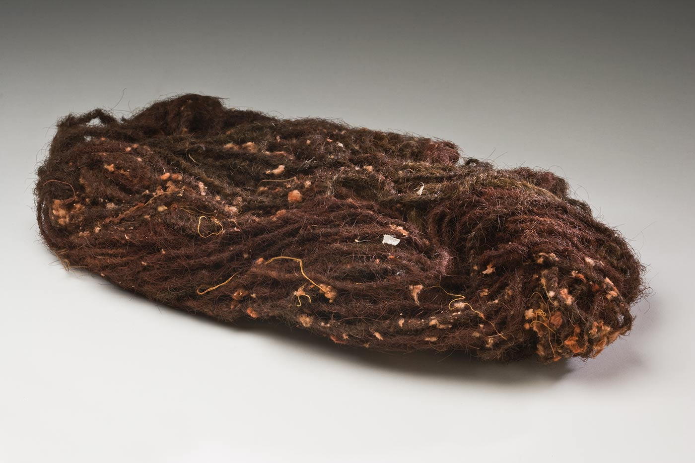 An oval bundle of red brown and dark brown two ply hair string with red pigment and off white tufts of plant fibre mixed through it. One end has a string coiled and tied around it.
