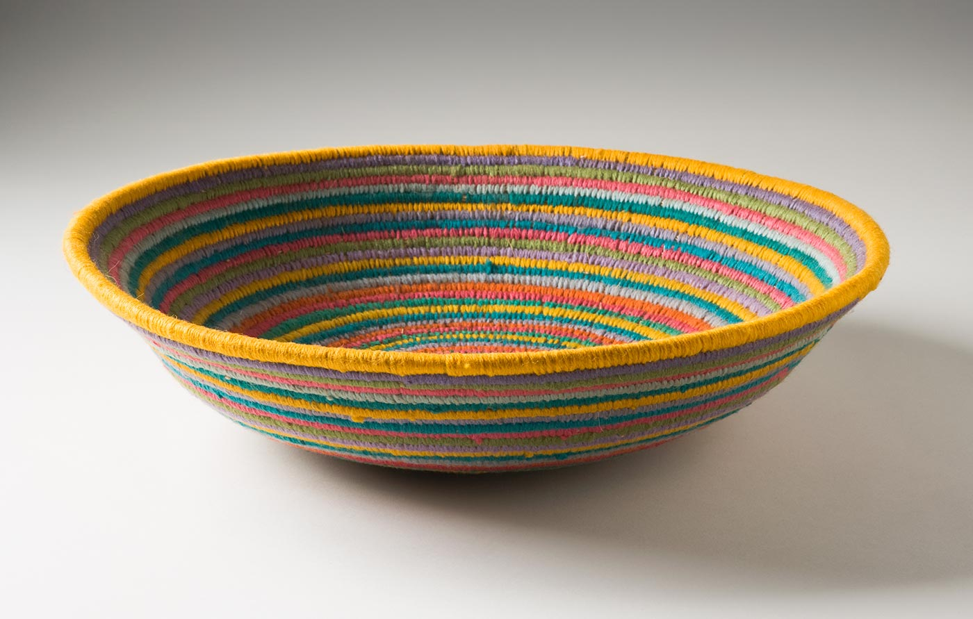 A multi-coloured circular coiled bowl-shaped basket made of yarn and plant fibre. The centre of the basket is in yellow yarn followed by horizontal stripes of yarn in lime green, lavender, pink, orange, yellow and light blue grey. - click to view larger image