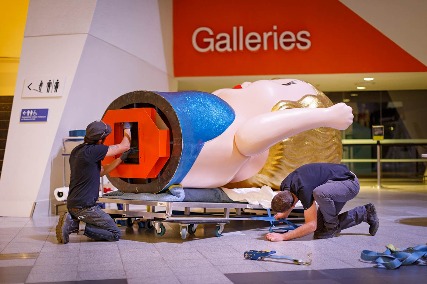 Colour photo of two men installing a large Kewpie doll in a gallery space. - click to view larger image