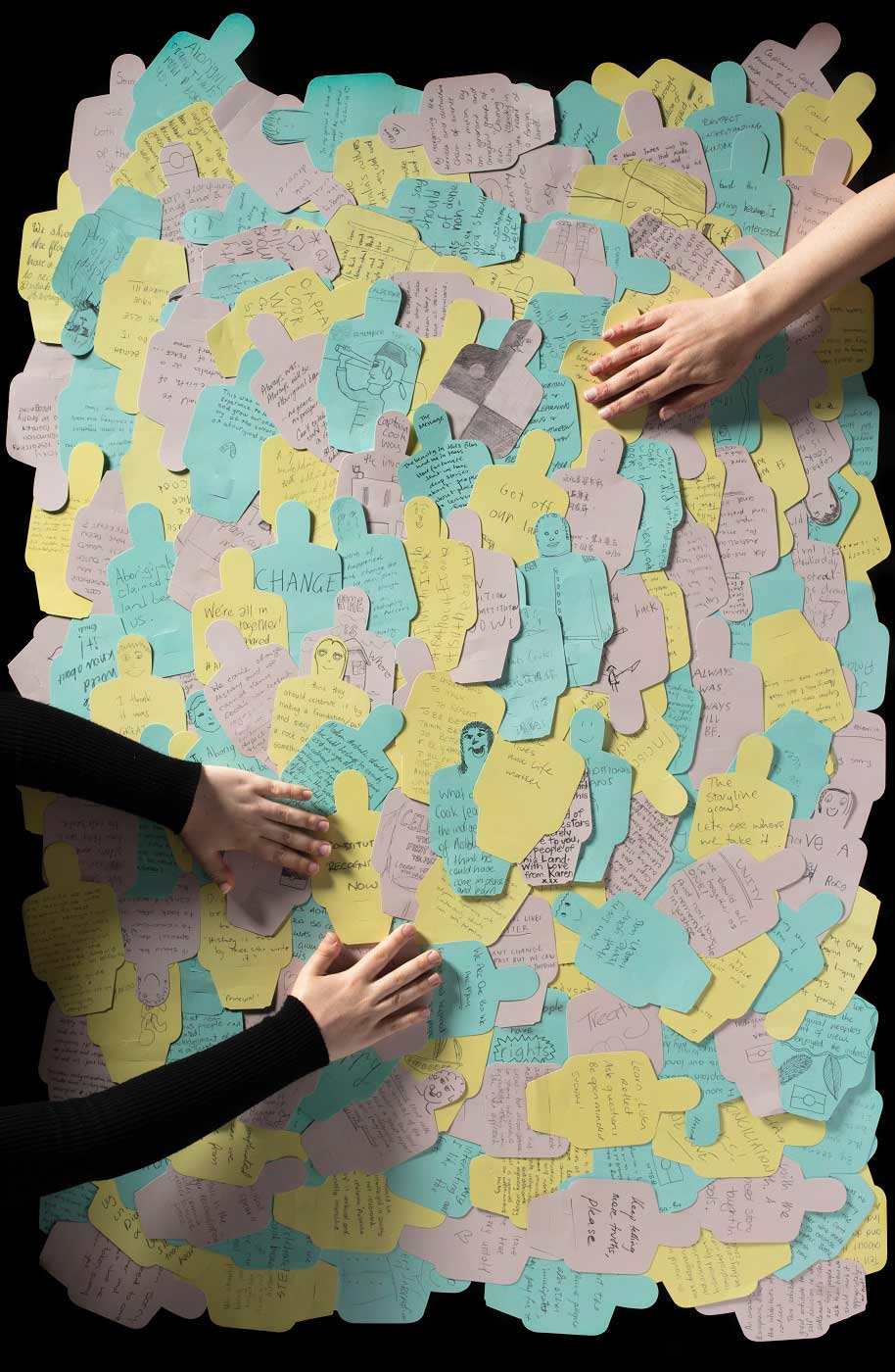 Two people sorting through a large amount of colourful paper figures featuring personalised messages. - click to view larger image