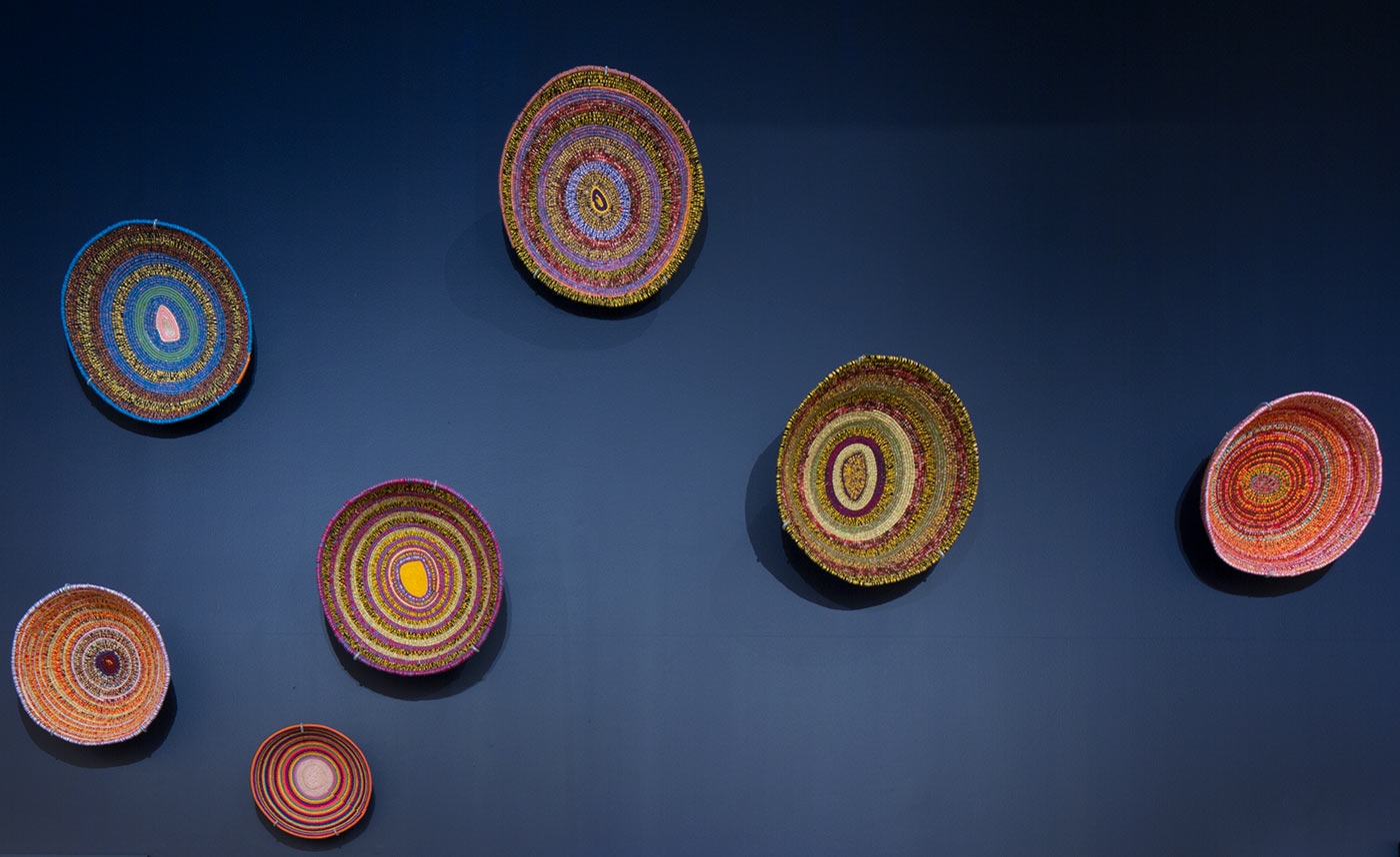 A display of seven baskets mounted on a wall.