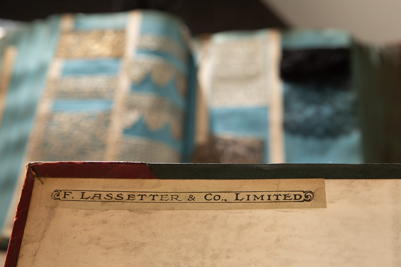 Colour photograph of a storage box with a label printed with the text: F. LASSETTER & CO., LIMITED. There is a blurred image in the background of textile samples. - click to view larger image