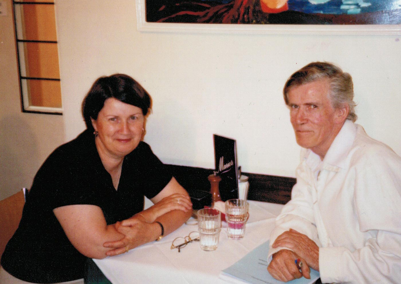 Colour photograph showing a man and woman sitting at a dining table. - click to view larger image