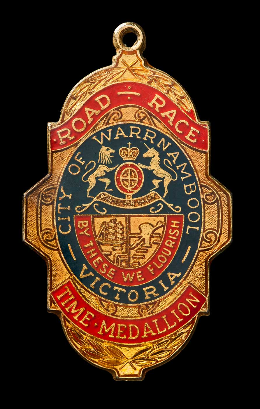 A gold coloured irregular shaped medallion. The front side has blue and red enamelled sections and is inscribed 'ROAD - RACE/CITY OF WARRNAMBOOL / BY THESE WE FLOURISH / VICTORIA / TIME MEDALLION'. - click to view larger image