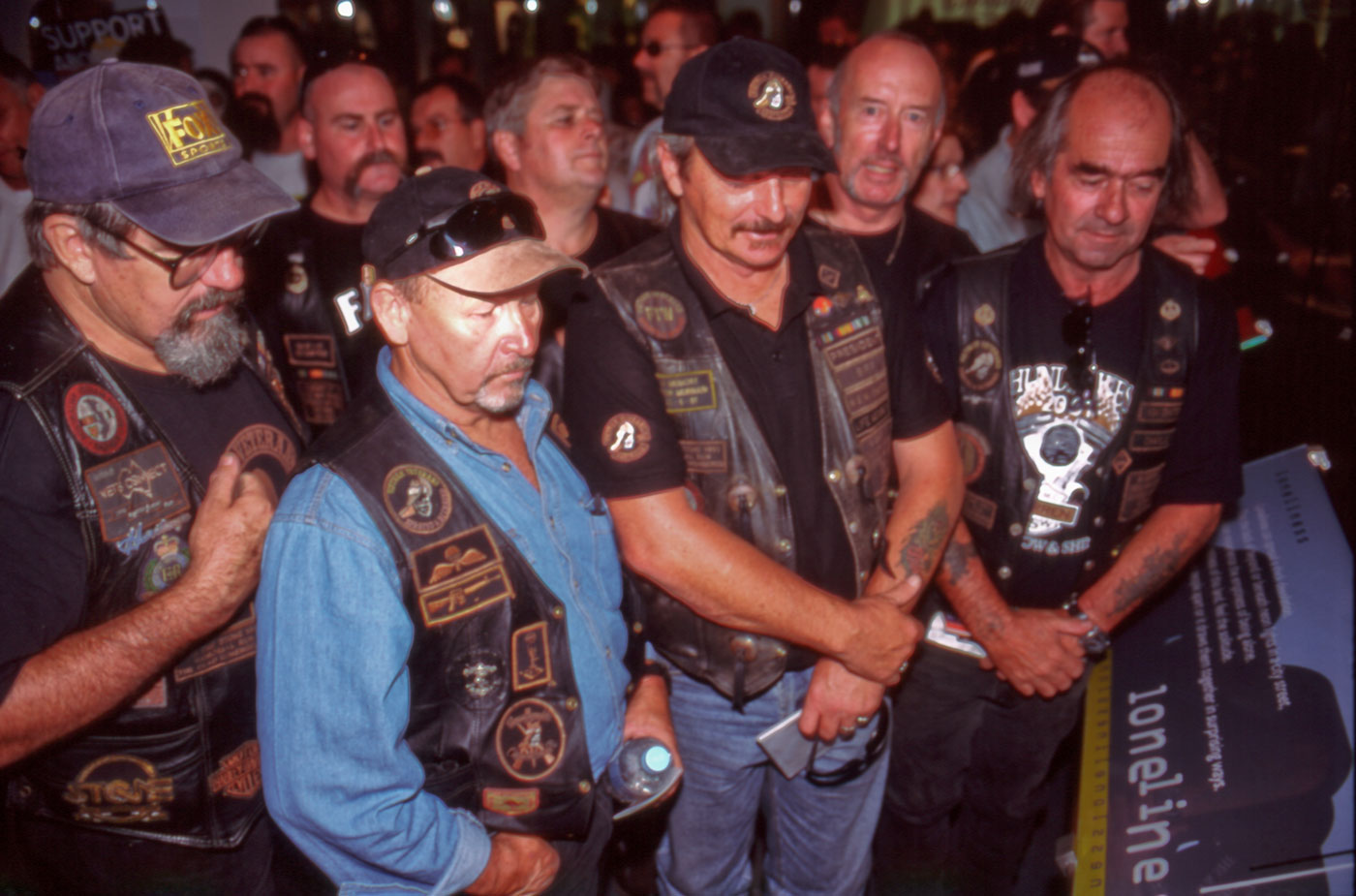Large group of men wearing leather jackets, inspecting an exhibition display - click to view larger image