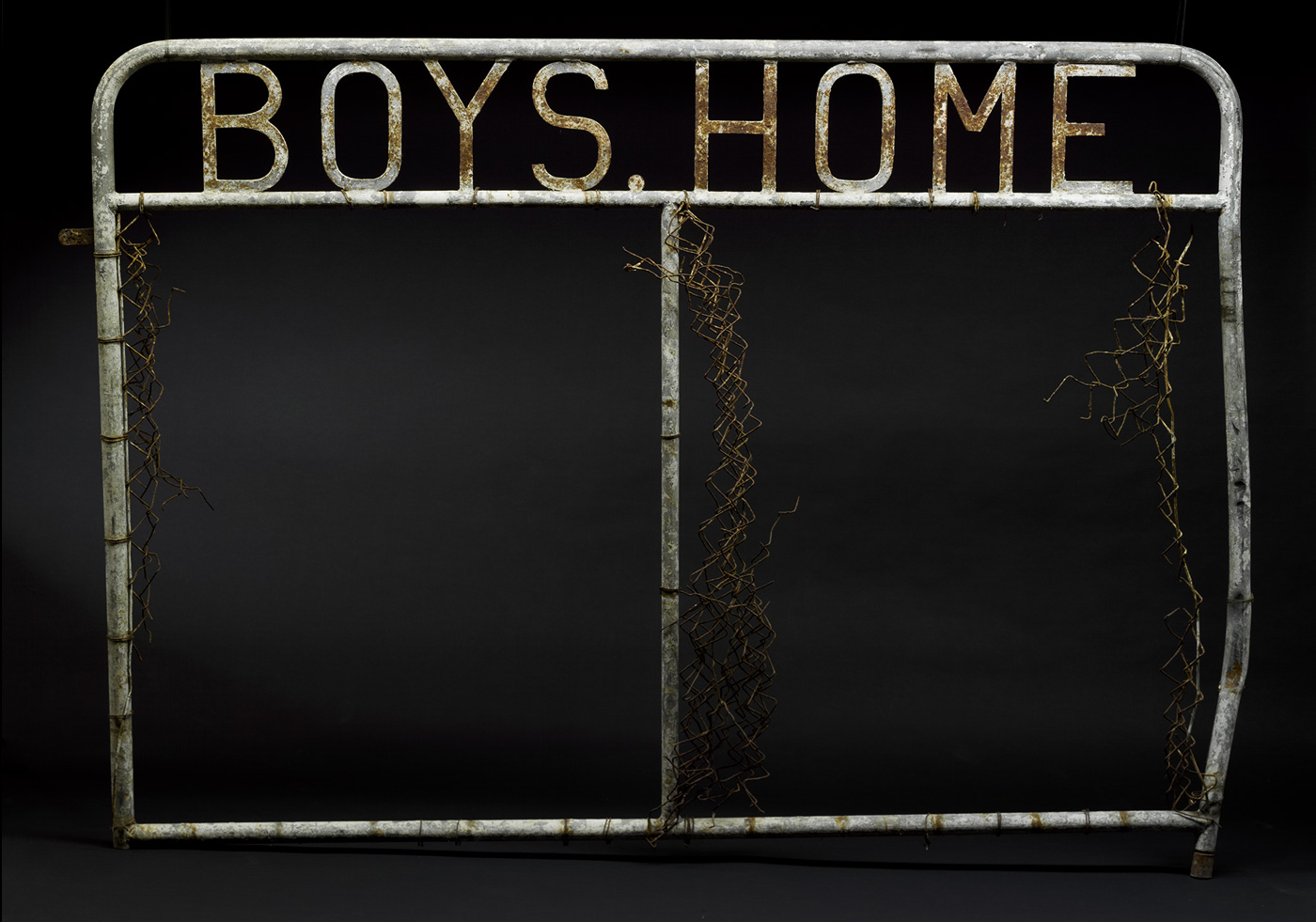 A metal gate panel with welded metal letters at the top which read 'BOYS HOME'. Remnants of wire mesh are attached to the tubular upright components of the gate, which are on the outer edges and in the centre. - click to view larger image