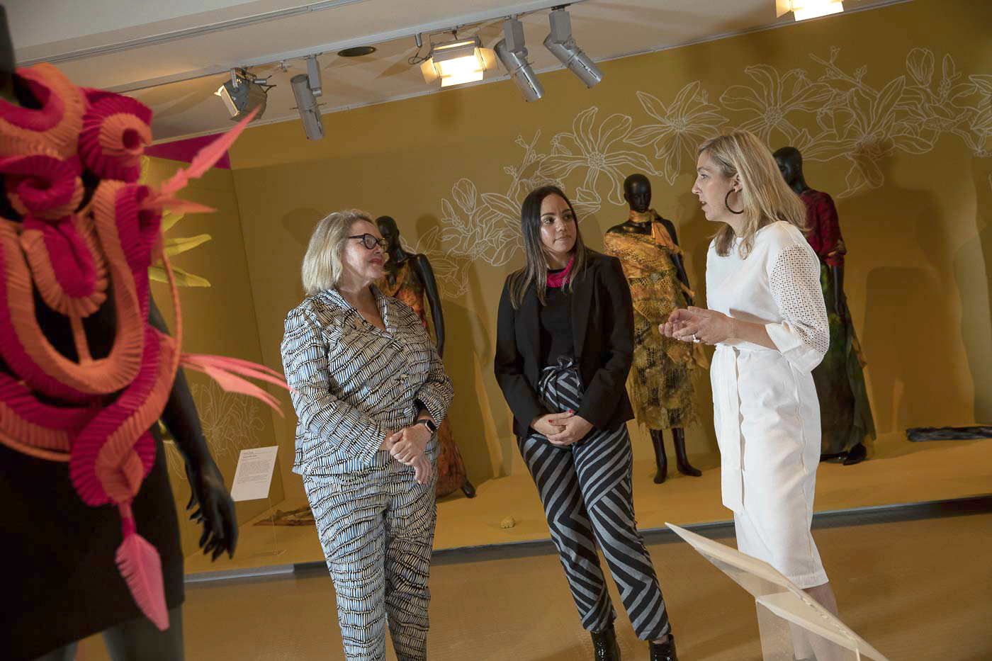 Three women are in discussion in an exhibition room with fashion clothing and accessories on display. - click to view larger image