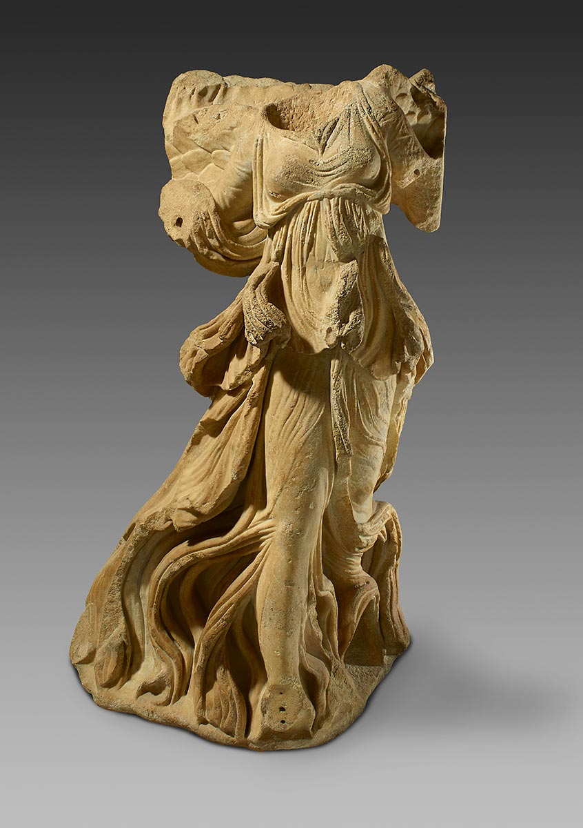 Marble statue of a woman with flowing robes. She is missing her head, arms and right foot. - click to view larger image