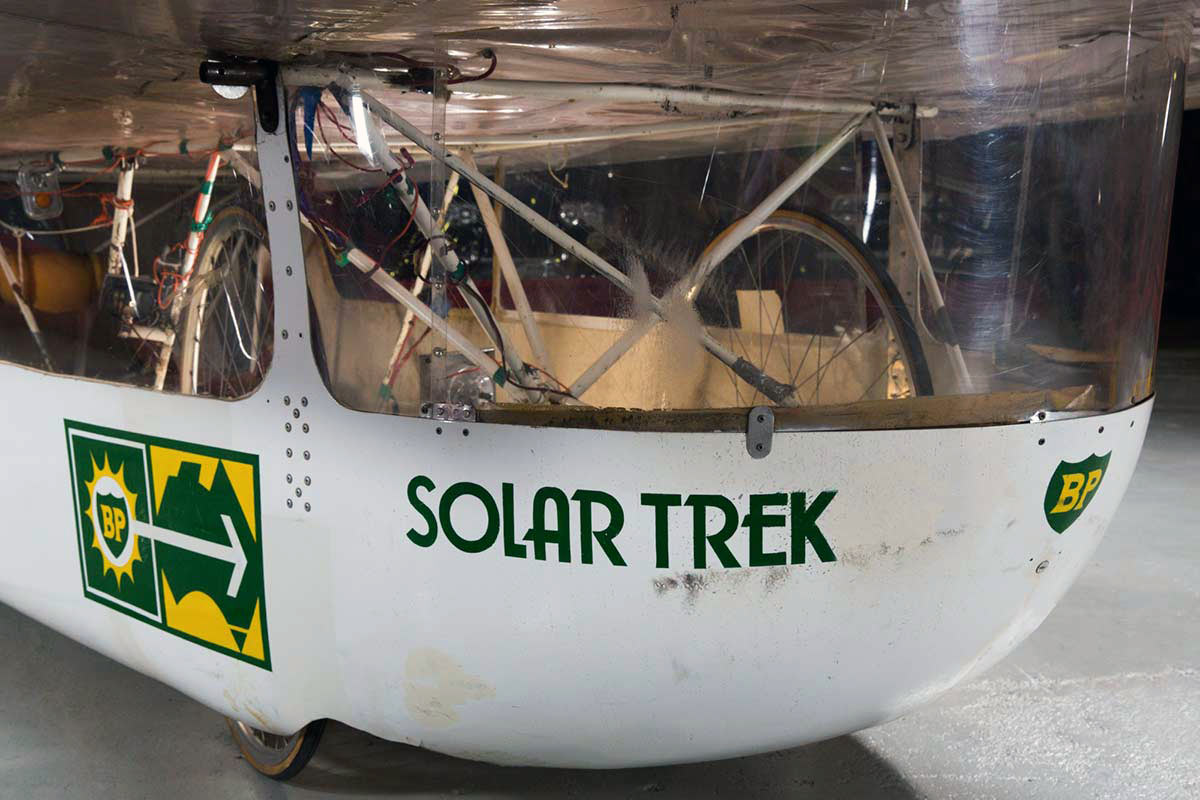Front view 0of a solar-powered vehicle clad in a white fibreglass, featuring bicycle fittings to the interior, and the text