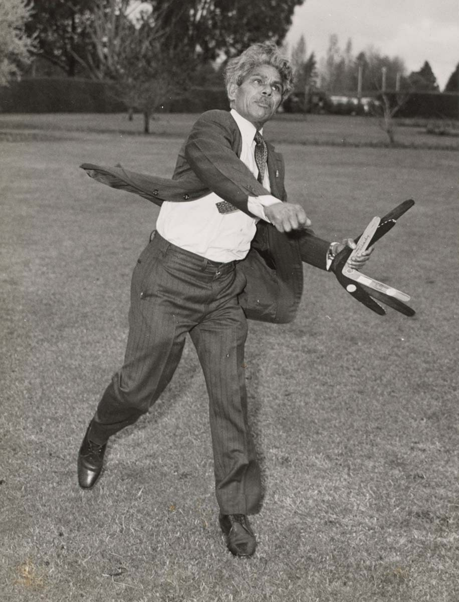 A black and white full length photograph of a man dressed in a suit [Neville Bonner] holding three boomerangs in his left hand after throwing one from his right hand. - click to view larger image