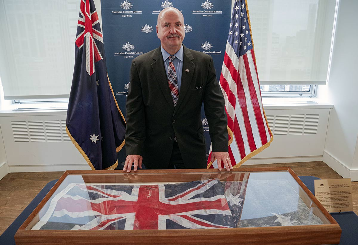 A man in a suit is standing behind a desk with a faded Australian flag in a large wooden display case. Behind him is the Australian and American and a banner for the Australian Consulate-General New York.
