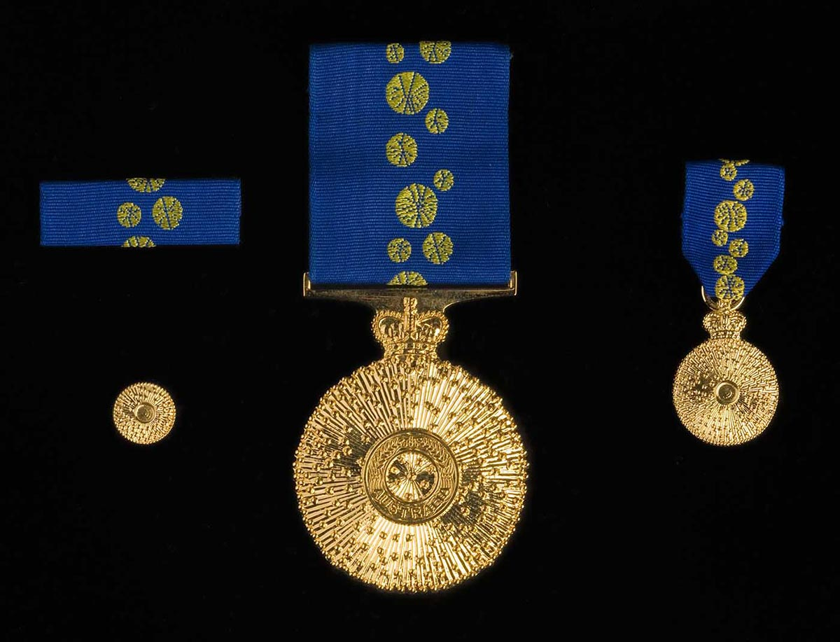 Order of Australia medals pictured on a black background. The two circular gold medals hang from blue ribbons with embroidered yellow wattle flowers. A similar ribbon sits above a small gold pin. - click to view larger image