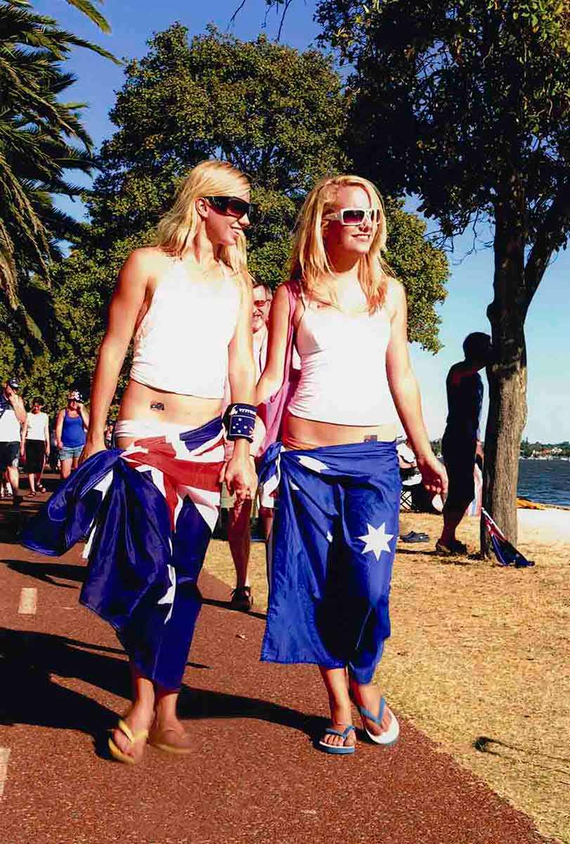A colour photograph of two young blonde-haired girls walking along the Perth foreshore on Australia Day in 2007. The girls are wearing sunglasses, thongs, sleeveless tops, and have Australian flags draped around their hips. Australian flag tattoos are visible on their torsos and one wears an Australian flag drink cooler on her wrist. - click to view larger image