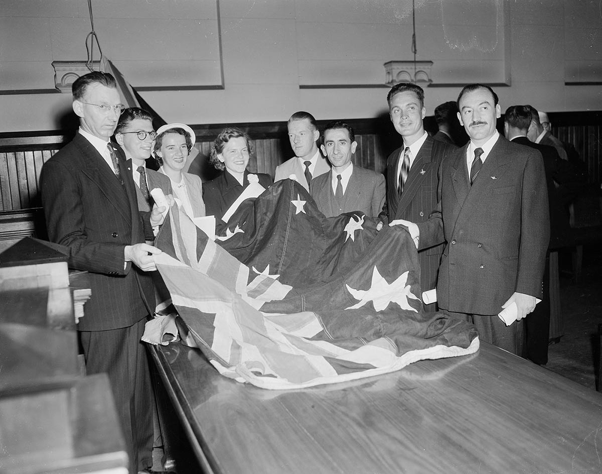 Six men and two women hold the edge of an Australian flag which is spread out across the far end of a table. - click to view larger image