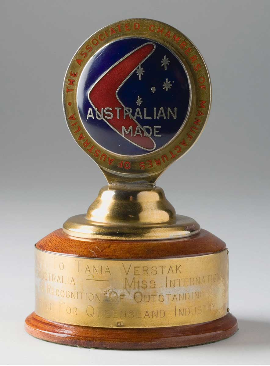 Trophy with a circular wooden base, topped with by a metal disc with 'Australian Made' written on it and an image of a boomerang and the five stars of the Southern Cross. A gold-coloured plate on the base reads: 'To Tania Verstak, Miss Australia-Miss International, in recognition of outstanding service for Queensland industry'. - click to view larger image