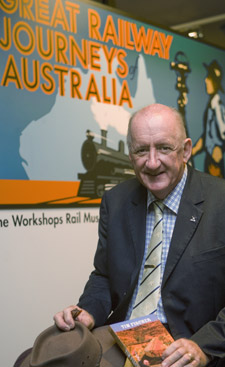 Tim Fischer, sitting holding his hat and and a book, in front of the Great Railway Journeys of Australia exhibition banner.