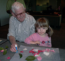 An elderly man and a young girl sitting at a table and doing a craft activity.