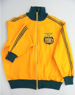 Long-sleeved yellow tracksuit jacket with high elasticated collar, waist and cuffs with zip fastener at front. Australian coat of arms badge sewn front, upper proper left with text above 'WORLD CUP / 1974'. Green stripe detail from shoulder to cuffs along sleeves