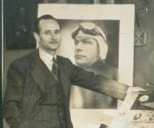 Austin Byrne standing before a portrait photo of aviator Charles Ulm