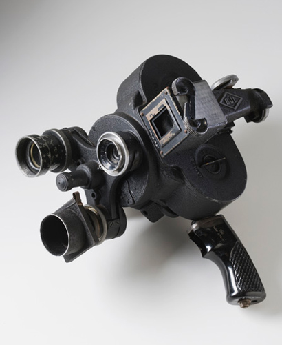 A black-coloured metal motion picture camera with three-lens turret, clockwork-driven film cartridge and side viewfinder. A black pistol-style handgrip extends beneath the camera body.