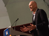 Side view of Peter Garrett standing behind a lectern.
