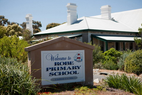A white sign, painted with 'Welcome to Robe Primary School' in blue, with an image of a red and white striped obelisk top right. The signs sits in a rock garden, beside a paved road, with a stone building visible in the background.