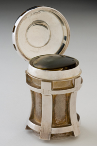 Captain James Cook's magnifier. A silver presentation case in the shape of a ship's capstan. There is an oval well inside the case, which accommodates the magnifying hand-lens.