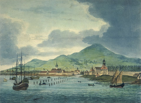 A harbour with ships in the foreground and mountains in the horizon.