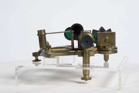 A sextant sitting upon a raised, clear plastic display base. The sextant has three 'legs', two short ones at each end and a longer one at the front toward the viewer. The long leg protrudes down through the display base. The sextant body is made up of a horizontal flat section upon which sits another flat section. On that part are vertical cylindrical and square sections. Above the long leg at the front rests a lense with an aperture on the end closest to the viewer. Behind the lense is a group of flat coloured glass lenses that apppear to be mounted so each one can be moved into position in front of the viewing lense. Much of the sextant is made from brass. The display base and the sextant sit in front of a featurless white backdrop. Shadows under the sextant suggest a light source off to the right-hand side of the image, beyond the frame.
