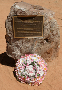 Commemoration plaque attached to a rock with a bouquet of flowers on the ground at the foot of the rock