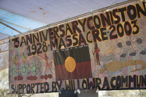Banner painted with Aboriginal designs and flag with the words: 75 Anniversary Coniston 1928 Massacre 2003. Supported by Willowra Community.