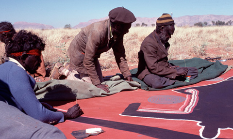 Men working on a painting in the desert.