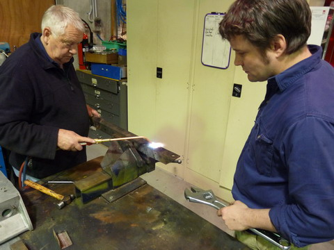 A man applies heat to a piece of metal, watched by another man, who holds a wrench.