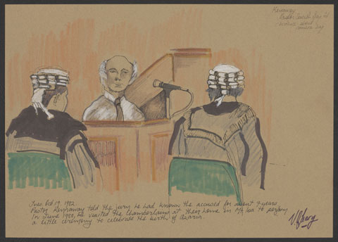 A man dressed in a white shirt and dark tie sits giving evidence in a courtroom. Two men in wigs and dark legal robes sit either side of him, facing the man.