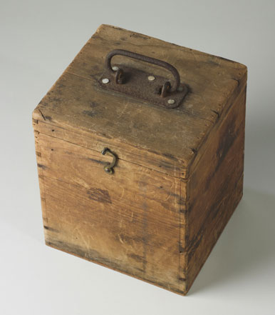Wooden box with a lid. It has a small metal latch hook at the front and a rusted metal handle on top.
