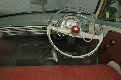 Interior view of the FJ featuring the dashboard, steering wheel and red leather upholstery.
