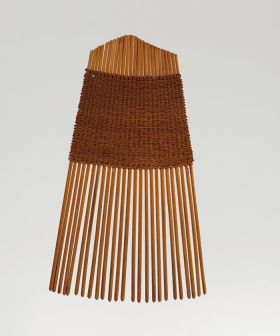 A comb made of twenty-five small sticks held together by a weave of light brown fibres.