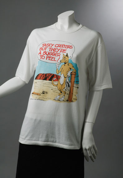 T-shirt with caricature of a dingo standing near Uluru, holding a baby's jumpsuit and saying 'Tasty critters but they're a bugger to peel!'