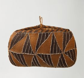 Oval-shaped basket made of coconut fibre and decorated with shells.