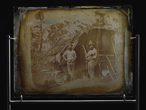 Two men stand outside a bark slab hut. Both men are wearing beards and hats. Various tools are leaning against the hut. A dog sits to the left of the first man.
