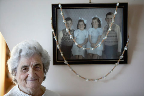 An older woman standing in front of a photograph on a wall. The photograph shows four children. A long necklace made from many small shells is draped over the photograph.