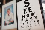 A poster at left in the style of an eye examination chart reads 'SEE HOW EASY IT IS TO GIVE TO THOSE WHO CAN'T'. A blurred portrait of Fred Hollows is on the right.