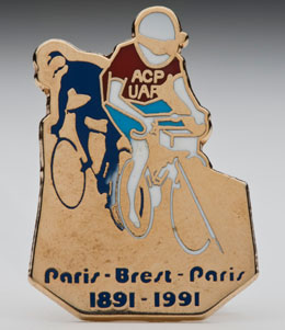 Gold badge with two cyclists at top and Paris-Brest_Paris 1891-1991 at bottom